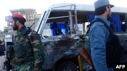 Afghan National Army (ANA) soldiers and Afghan police stand next to a damaged military bus following an explosion in western Kabul.