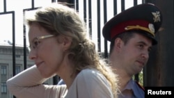 Russian opposition figure and TV host Ksenia Sobchak (left) arrives for questioning at the Russian Investigative Committee on June 15.