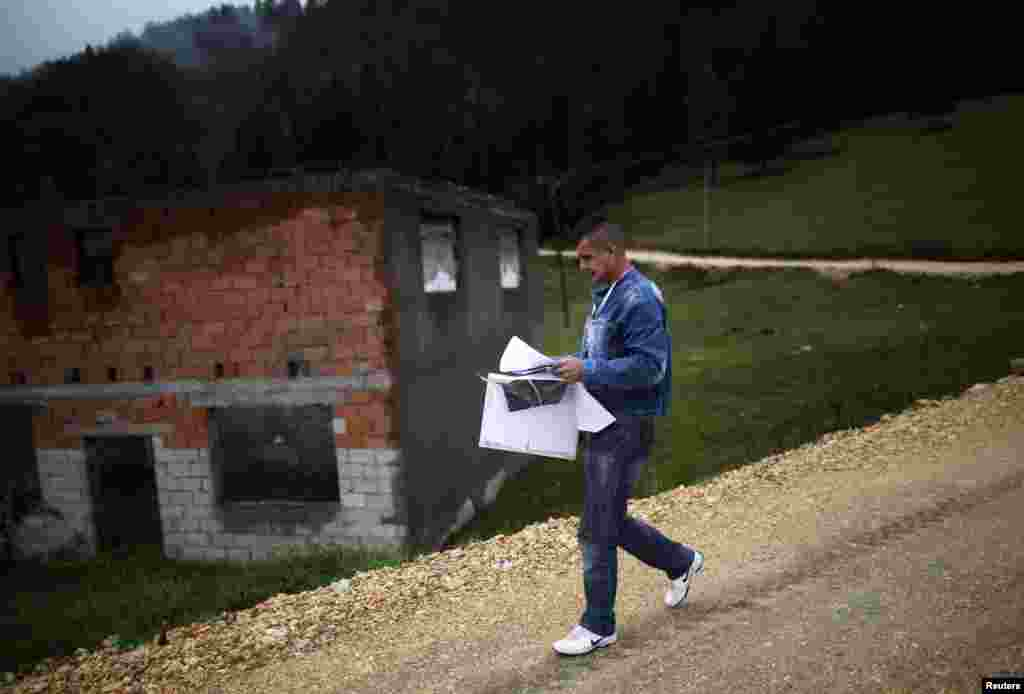 Surveyer Elvis Spijudic walks near houses destroyed during the 1992-95 war as he reads a map before interviews during Bosnia's first census in the village Krusev Do, near Srebrenica. (Reuters/Dado Ruvic)