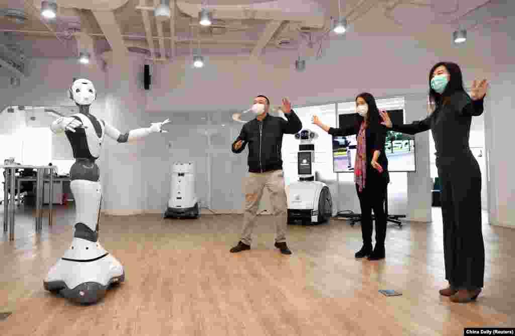 СпівробітникиCloudMinds Technologies стоять поруч із роботом із підтримкою 5G. До його функцій входить надання медичних порад, пов'язаних із новим коронавірусом. Пекін, Китай