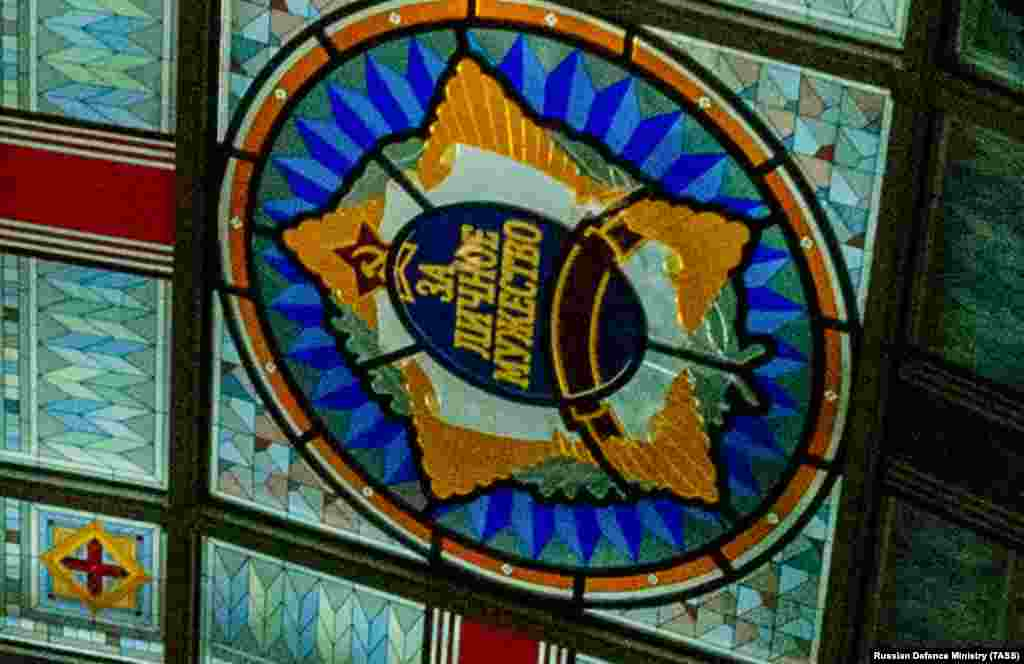 """A close-up of the emblem with the words """"for personal courage"""" and a partially obscured communist insignia."""