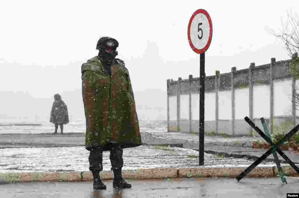 Armed men, believed to be Russian servicemen, stand guard outside a Ukrainian military base in Perevalnoye.