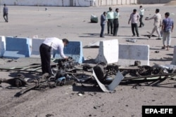 Police inspect the wreckage of the car bomb.
