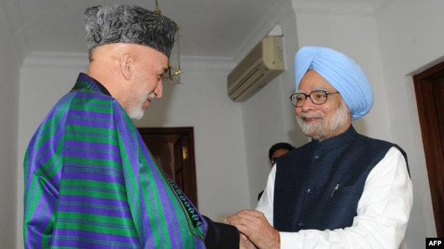 Indian Prime Minister Manmohan Singh (right) shakes hands with Afghan President Hamid Karzai in New Delhi on December 13.