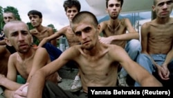 In this photo by Yannis Behrakis, emaciated Muslim refugees, released from a Croat prison, wait for lunch in Jablanica, central Bosnia, in September 1993.