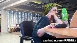 Kompýuteriň başynda oturan bir zenan maşgala.