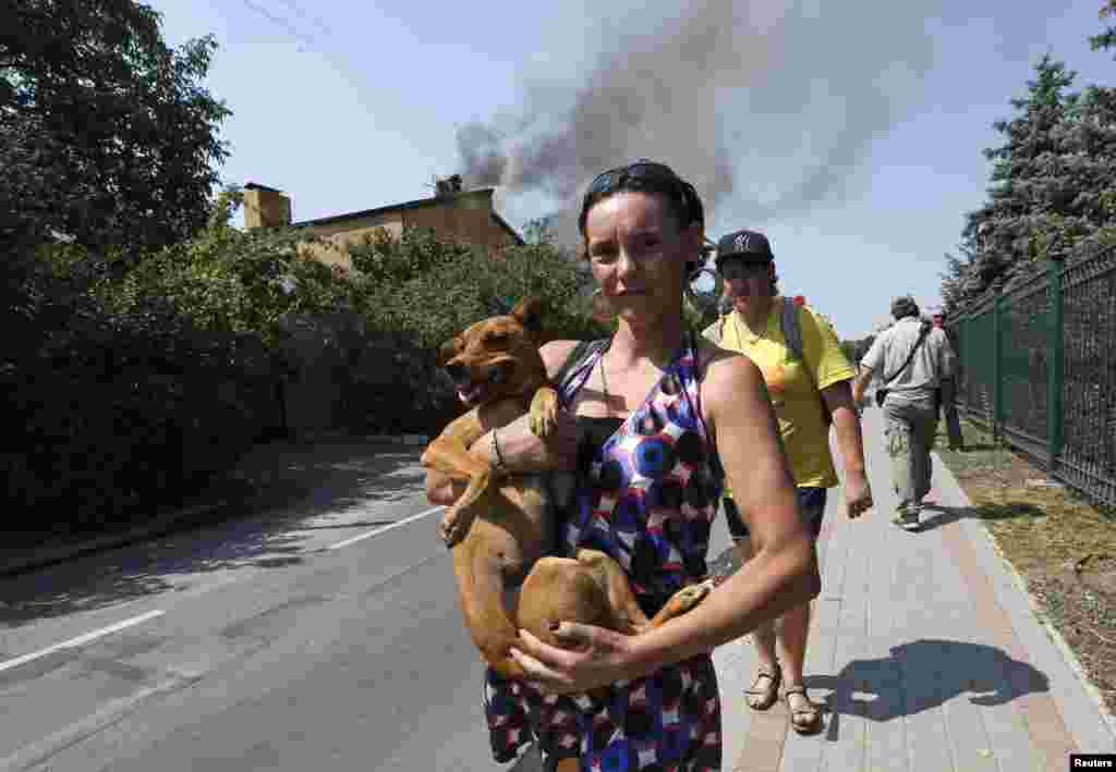 A woman carries a dog as smokes rises above buildings shortly after a shelling in Donetsk in August 2014.