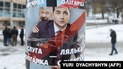 A placard depicting Ukrainian entertainer and presidential candidate Volodymyr Zelenskiy (right) as a puppet for oligarch Ihor Kolomoyskiy in Lviv in February.