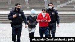 Московские полицейские сопровождают задержанных в отделение для проверки документов (архив)