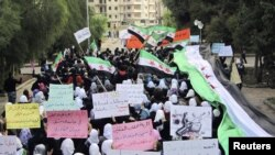 Antigovernment demonstrators march in the town of Homs, one of the most restive Syrian cities, in late November.