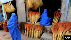 Afghanistan -- Afghan shoppers look for brooms at a roadside shop in Herat, April 9, 2014