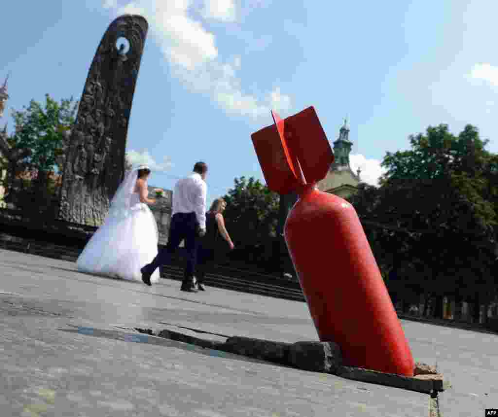 A newly married couple walks past an art installation showing an unexploded bomb, set near the Taras Shevchenko monument (left) in the center of the western Ukrainian city of Lviv, close to Poland's border. (AFP/Yurko Dyachyshyn)