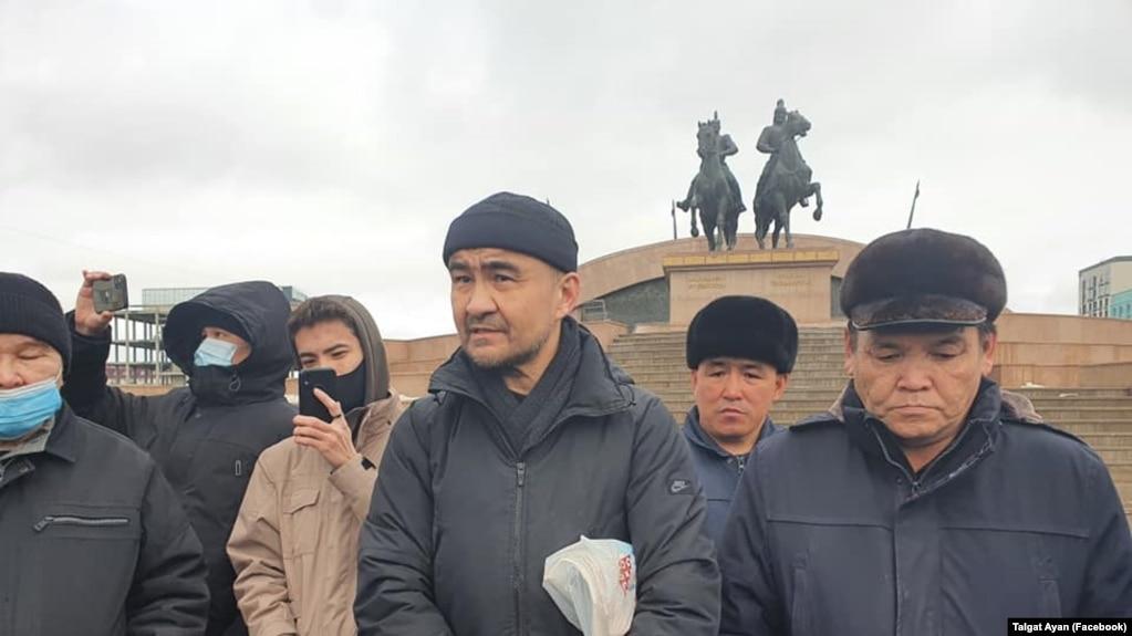 Макс Бокаев (в центре) стоит на площади в Атырау. 28 февраля 2021 года.