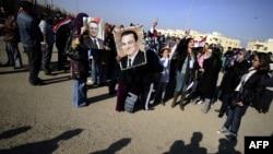 Хосни Мүбәракты жақтаушылар Каирдегі оның соты болып жатқан полиция академиясының сыртында Мүбәракқа қолдау білдіріп тұр. Каир, 28 желтоқсан 2011 жыл.