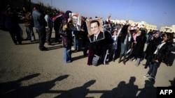 Сторонники бывшего президента Хосни Мубарака стоят перед зданием полицейской академии, где проходит суд над ним. Каир, 28 декабря 2011 года.