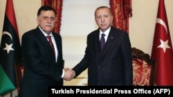 Turkish President Recep Tayyip Erdogan (right) meets with Fayez al-Sarraf, the head of the Tripoli-based Government of National Accord, in Istanbul on December 15.