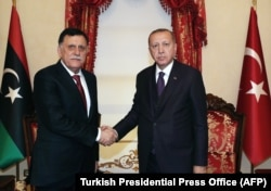 Turkish President Recep Tayyip Erdogan (right) meets with Fayez al-Sarraj, the head of the Tripoli-based Government of National Accord, in Istanbul on December 15.