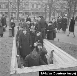 Жінка плаче, спускаючись разом з іншими жителями Гельсінкі у бомбосховище
