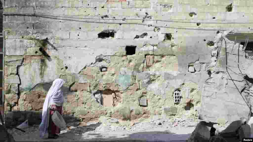 A Syrian woman walks past a building damaged by fighting in the Qaboun district of Damascus on July 31. (Reuters/Omar  al-Khani)