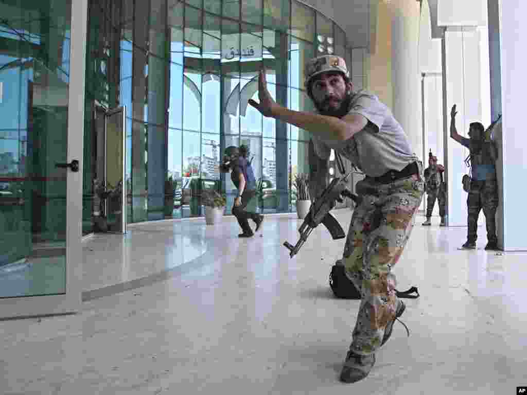 Libyan rebel fighters and a television cameraman take shelter as an intense gun battle erupted outside the Corinthia Hotel, where many foreign journalists stayed.