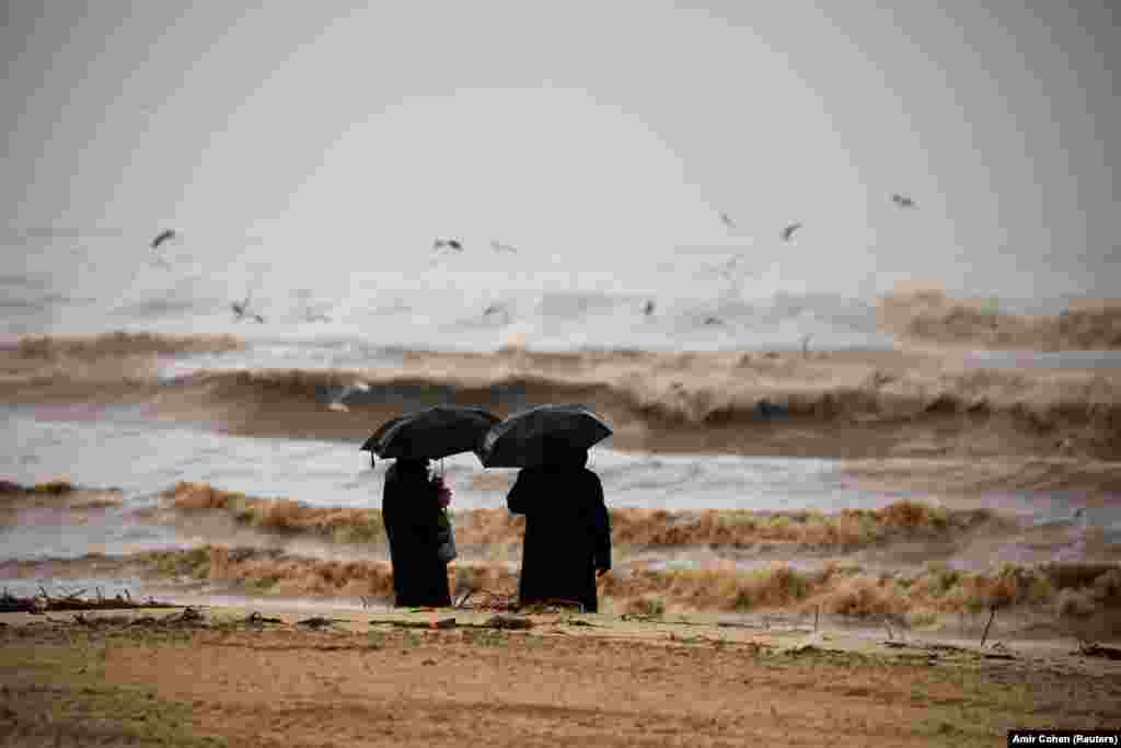 Ultra-Orthodox Jewish men hold umbrellas and look at the Mediterranean Sea as heavy rainfalls hit Ashdod in Israel. (Reuters/Amir Cohen)