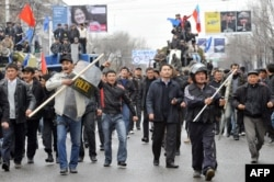 Сторонники кыргызской оппозиции идут по улице в центре Бишкека. 7 апреля 2010 года.