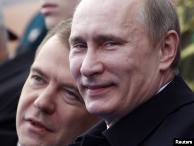 Russia -- President Dmitry Medvedev (L) and Prime Minister Vladimir Putin speak as they watch a military parade on Red Square on Victory Day in Moscow, 09May2011