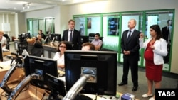 Главный редактор канала Russia Тoday Маргарита Симоньян (справа) сопровождает президента России Владимира Путина во время его визита в новый студийный комплекс телеканала. Москва, 11 июня 2013 года.