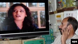 An Afghan man watches an Indian soap opera at his TV shop in Kabul. The Afghan culture minister said that female newsreaders should appear different from actresses in movies and soap operas.