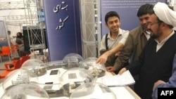 Студенттер даражалуу диниятчини Ирандын ядролук өнөр жайдагы жетишкендиктерине арналган көргөзмө менен тааныштырышууда.Шахид Бехешти университети, Тегеран. 20-апрель 2009