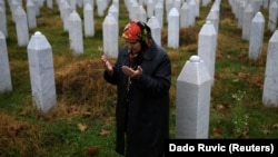 Hatidza Mehmedovic prays near the graves of her two sons and husband at the Memorial Center in Potocari, near Srebrenica, on November 14, 2017.
