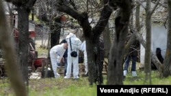 Officers investigate the site of the shootings in the village of Velika Ivanca, about 40 kilometers southwest of Belgrade.