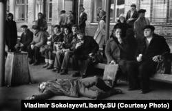 A man dozes on the pavement at a Novokuznetsk bus stop.