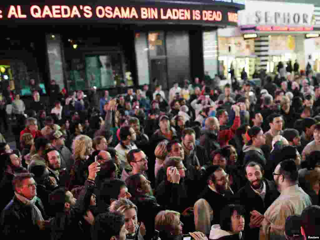 A news ticker displays information on Al-Qaeda leader Osama bin Laden's death in Pakistan as people attend a spontaneous celebration in New York's Times Square.