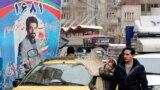 A couple walks past an electoral billboard in a street in Tehran, February 17, 2020