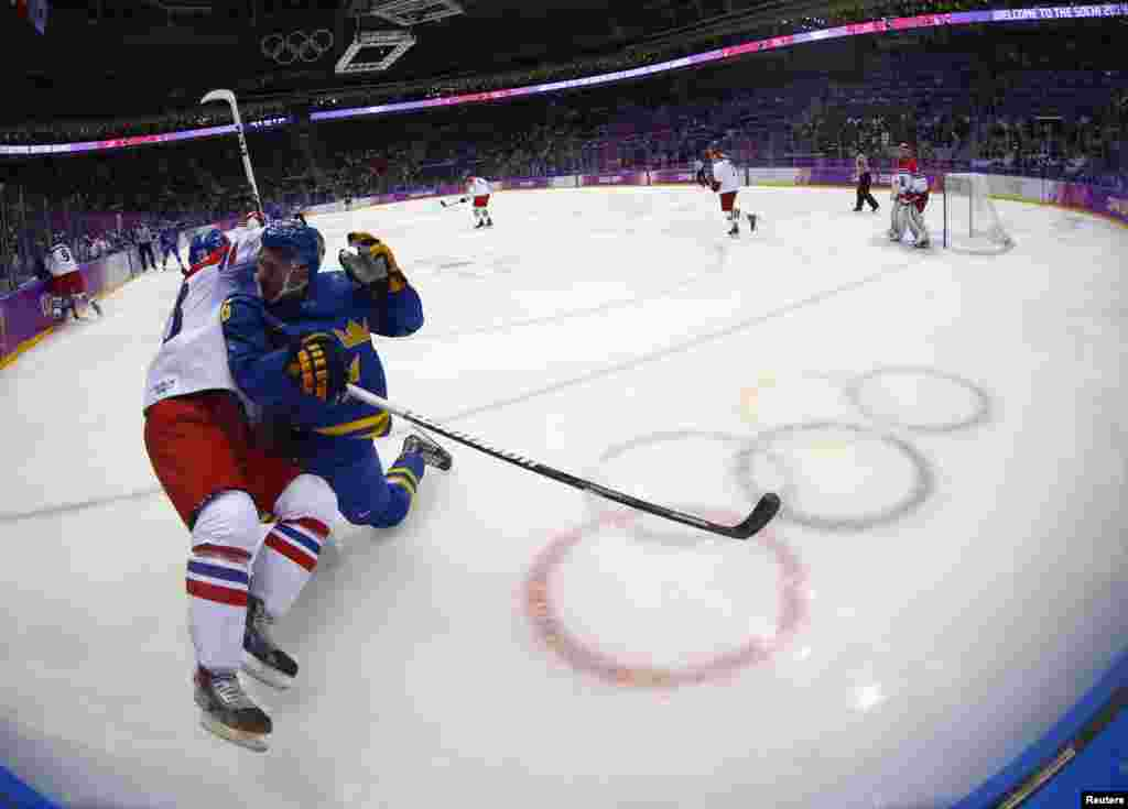 Zbynek Michalek (left) of the Czech Republic (in white) battles with Sweden's Marcus Kruger in the corner during the first period of their men's preliminary-round ice-hockey game.