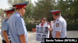 Гражданский активист Асель Нургазиева держит плакаты перед акиматом Жанаозена с фотографиями жителей, погибших во время событий в декабре 2011 года. Многомесячная забастовка нефтяников закончилась тем, что полицейские открыли огонь по демонстрантам. 29 августа 2012 года.