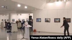 Ресей елшісіне қастандық жасаушы адам құлап түскен Андрей Карловтың қасында тұр. Анкара, 19 желтоқсан 2016 жыл