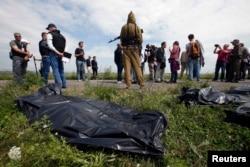 Черные мешки с телами погибших на месте крушения рейса MH17