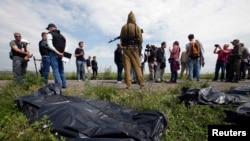 Эксперты ОБСЕ, журналисты и сепаратисты на фоне упакованных в пакеты останков погибших в результате авиакатастрофы малайзийского лайнера. Донецкая область Украины, 19 июля 2014 года.