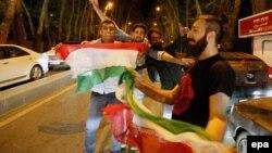 Иранцы с национальным флагом Ирана в руках празднуют достижение предварительного соглашения между Ираном и шестью лидирующим странами. 2 апреля 2015 года.