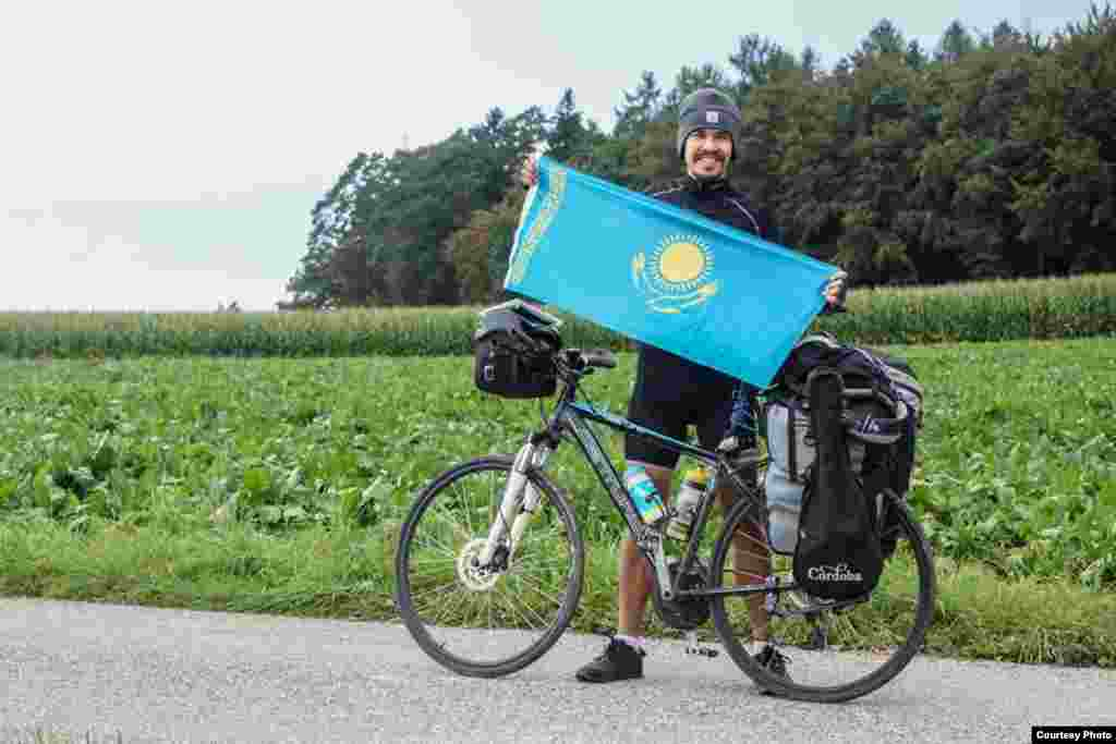 Мағжан Сағымбаев әлемді велосипедпен аралаған саяхатында Қазақстан туын бірге алып жүрді.