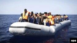 Нелегальных мигрантов из Африки перевозят на спасательных лодках итальянских ВМС после крушения корабля, на котором они находились. Средиземное море, сентябрь 2014 года.