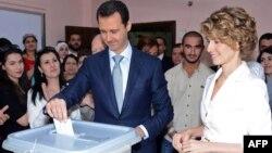 Башар ал-Асад (ортодо) жубайы Асма ал-Асад менен Дамасктагы шайлооканада, 3-июнь, 2014