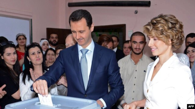 President Bashar al-Assad (center) and his wife Asma al-Assad (R) cast their votes at a polling station in Damascus on June 3.