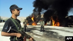 Pakistani policemen stand beside burning trucks that were carrying NATO fuel supplies after an attack by suspected Taliban militants in November.