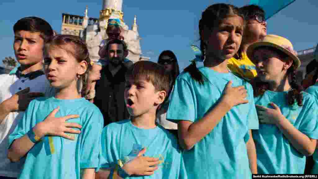 Діти тримають руки на серці під час виконання гімну