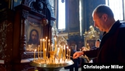 A man lights candles inside St. Volodymyr's Cathedral in Kyiv.