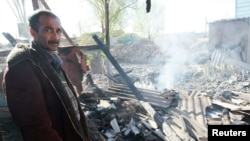 A local resident stands by his burned down house in the settlement of Maevka outside Bishkek, following ethnic clashes there last year