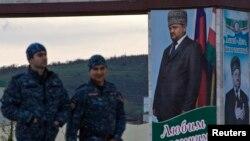 Javna služba obezbeđenja prolazi pored plakata bivšeg predsednika Čečenije Ahmada Kadirova, 2013.